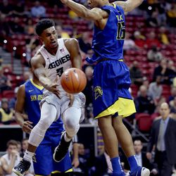 Utah State Aggies Julian Pearre passes the ball against San Jose State Spartans' 15 Brandon Clarke at the Mountain West Men's Basketball Championships at the Thomas & Mack Center, Las Vegas, Nevada on Wednesday, March 8, 2017.