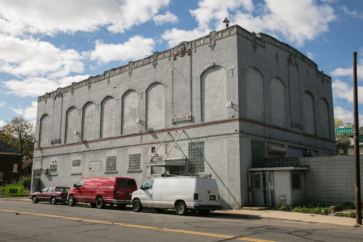 Exterior of a two-story, rectangular, gray-brick building. The second-story windows have all been covered. A red van and white van are parked outside the entrance.