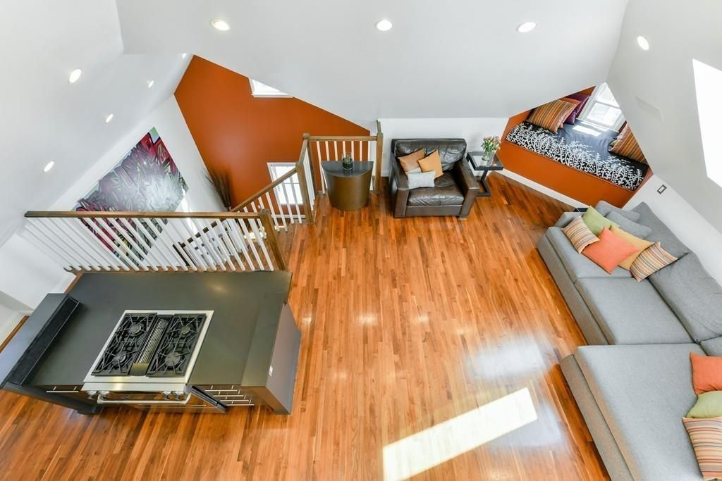 An aerial view of an open living room and kitchen from vaulted ceilings.