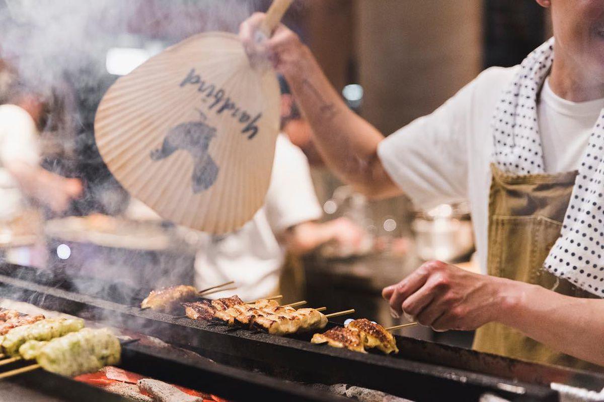 Yardbird Hong Kong chicken skewers cooking over fan