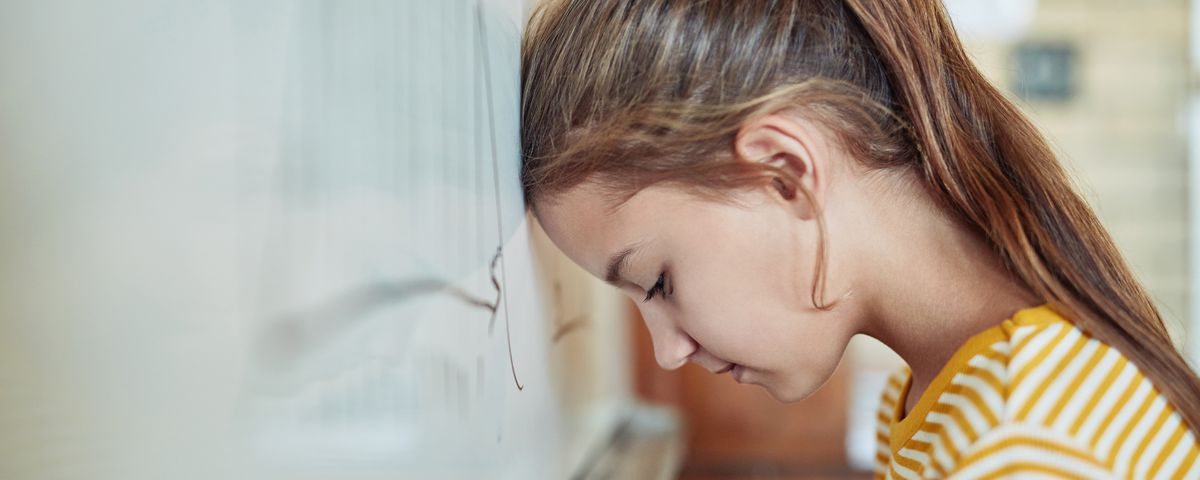 A young girl leaning against a board in a classroom at school.