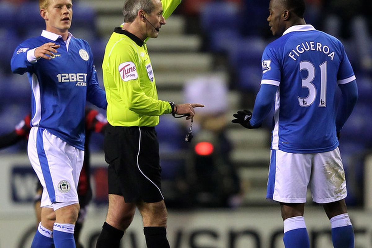 You Plonker! Referee Martin Atkinson books Figueroa for a blatant hand ball to add to the referees comedy of errors on the night.