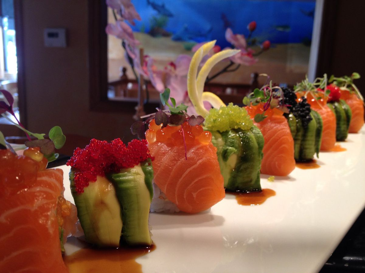 A lineup of sushi pieces sit on a long white plate