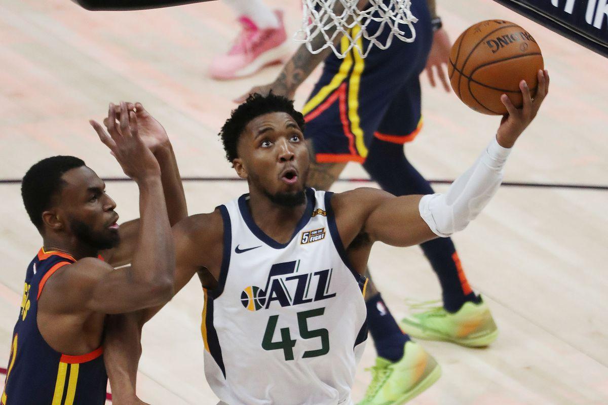 Utah Jazz guard Donovan Mitchell (45) drives against Golden State Warriors forward Andrew Wiggins (22)in Salt Lake City on Saturday, Jan. 23, 2021.