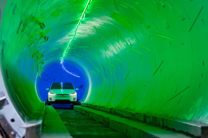 A white car fitted with tiny wheels locking it onto cement track is seen at the end of a bright green and blue tunnel.