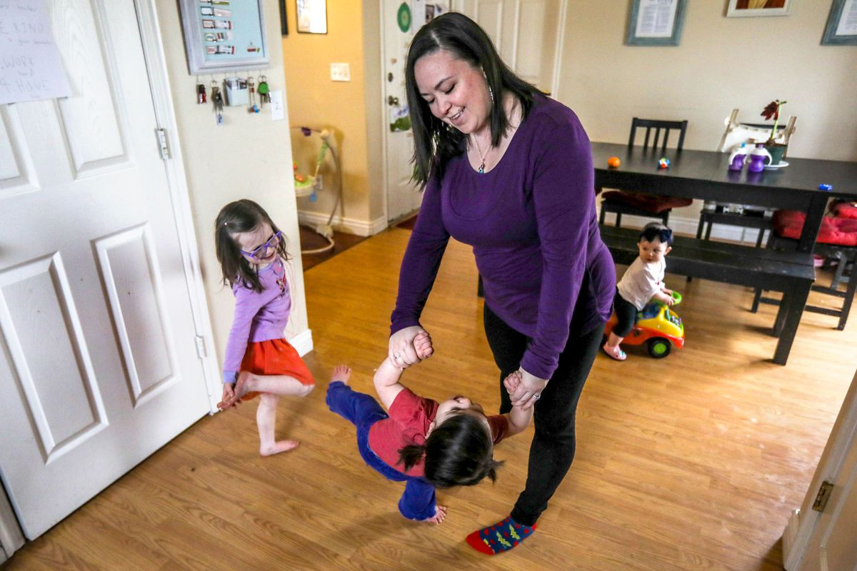 Dani Reed, center, swings Quinley while Lina watches in their home in Eagle Mountain on Saturday, March 20, 2021. At 35 weeks pregnant soon after the pandemic started, Reed switched her birth plan to have a home birth so her family could be there.