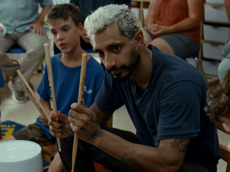 A man sits holding drumsticks to show a group of children.
