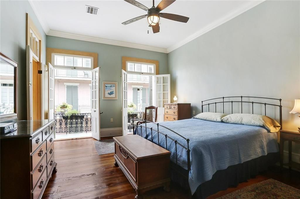 Two French doors open to a balcony in as master bedroom with dark wood floors and a king bed with blue bedding.