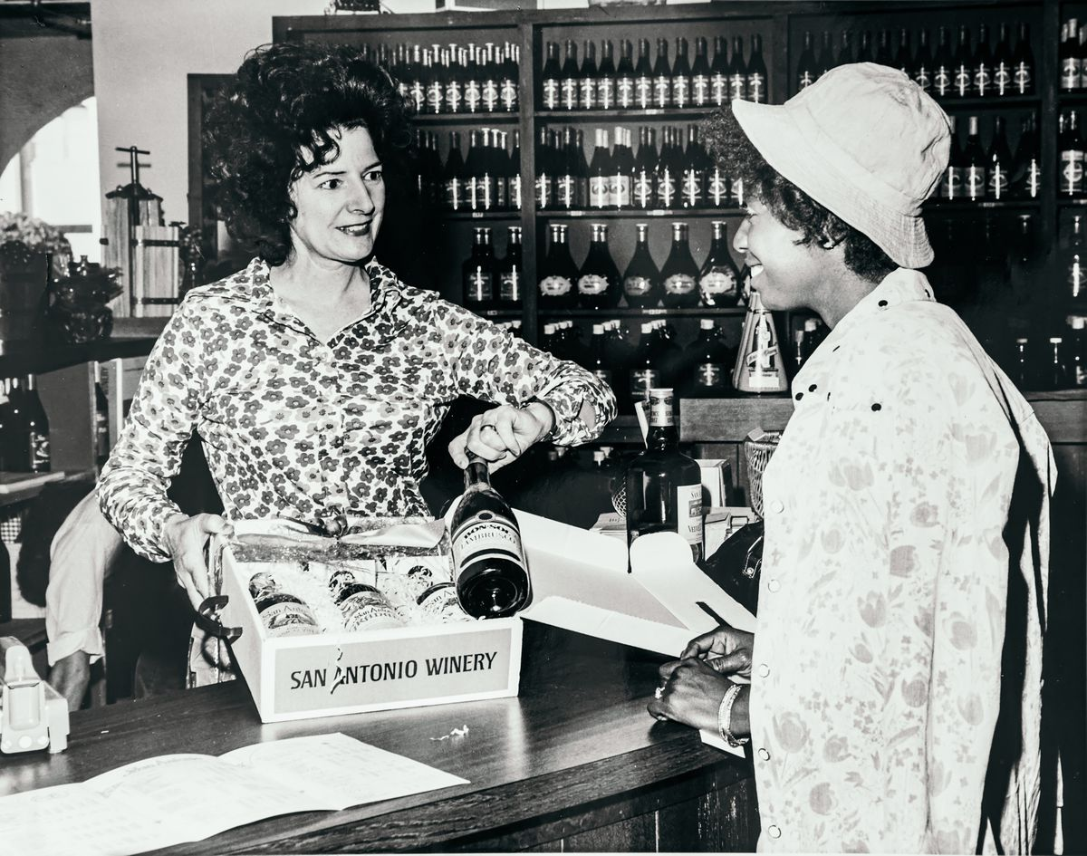 Maddalena Riboli with a customer at San Antonio Winery, showing her a bottle from a box.