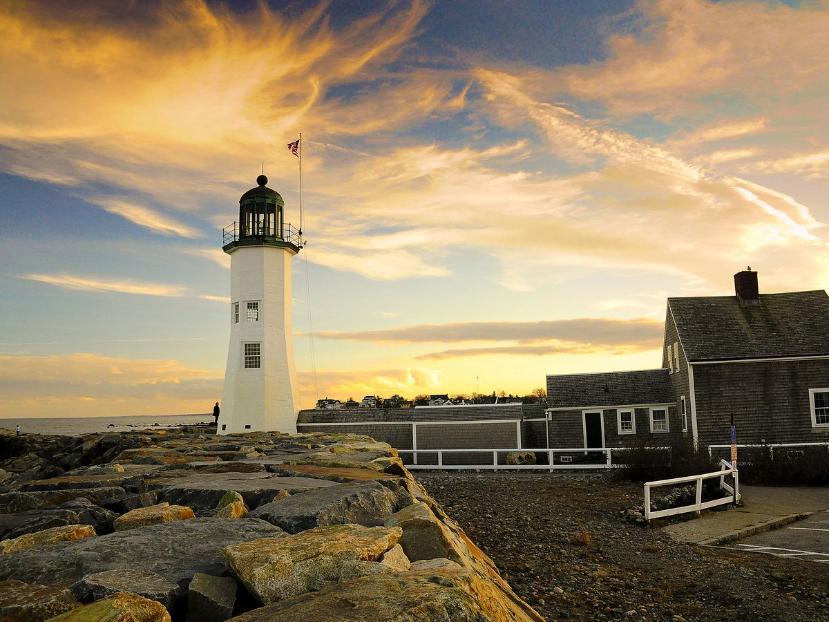 A white lighthouse overlooking the ocean next to a clapboard home, while the sun is setting
