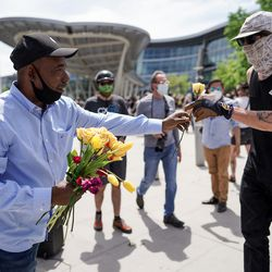 The Rev. Jay Ragsdale, of the Fill the Pot Ministry of the Calvary Baptist Church, hands out flowers to people in Salt Lake City on Saturday, May 30, 2020, as they protest the death of George Floyd, who died while being taken into custody by police in Minneapolis.