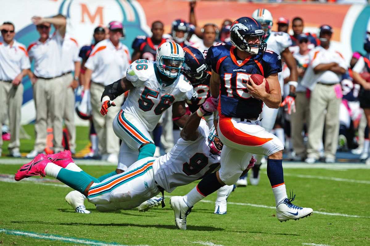 MIAMI GARDENS, FL - OCTOBER 23: Tim Tebow #15 of the Denver Broncos carries the ball against Cameron Wake #91 of the Miami Dolphins at Sun Life Stadium on October 23, 2011 in Miami Gardens, Florida. (Photo by Scott Cunningham/Getty Images)