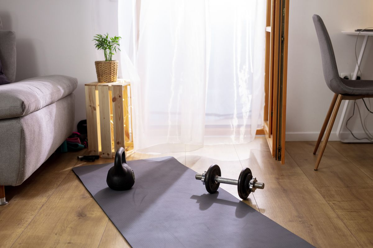 A yoga mat with weights set up in a living room.