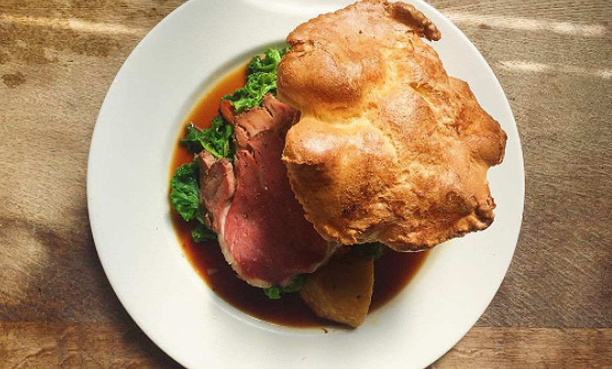 A birdseye view of roast beef and Yorkshire pudding, billowing up, on a white plate on a wooden pub table