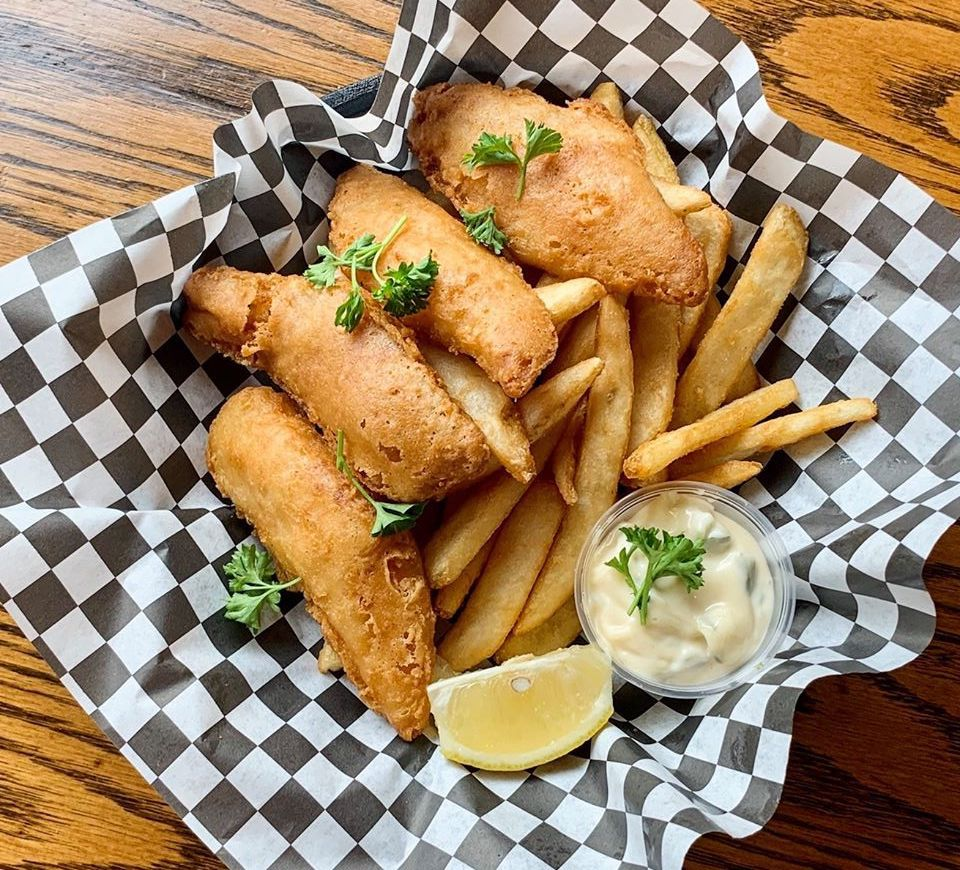 A basket of four fried fish fillets and French fries