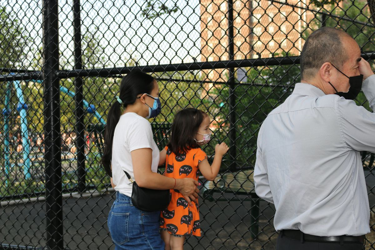 A mother waves goodbye to her son through a fence as he starts his first day of kindergarten. She is holding her young daughter as she grabs onto the fence.