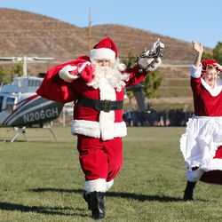 Santa and Mrs. Claus waves as Santa Flight volunteers bearing Christmas gifts land in Hurricane on Wednesday, Dec. 7, 2016. Pilots with the Utah Wing of Angel Flight West filled 16 aircraft with 7,000 pounds toys, school supplies, books, backpacks and warm clothing for students at Hurricane Elementary School. The items were gathered by 16 Boy Scouts as part of their Eagle Scout service project. Since the first Santa Flight in 2000, members of the Utah Wing have worked with their local communities to gather needed supplies and toys, and deliver them to Title I schools in rural communities throughout Utah.