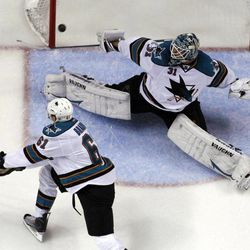 A puck shot by St. Louis Blues' David Backes, not shown, scores past San Jose Sharks goalie Antti Niemi, of Finland, and Justin Braun (61) during the second period in Game 2 of an NHL Stanley Cup first-round hockey playoff series Saturday, April 14, 2012, in St. Louis.