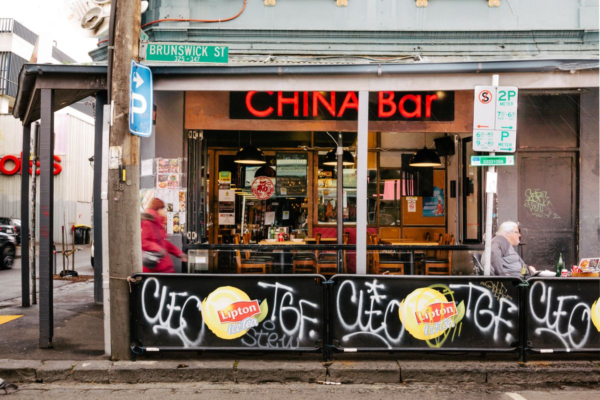 China Bar signage peeks out from under an awning. In front of the restaurant are barriers covered in graffiti.