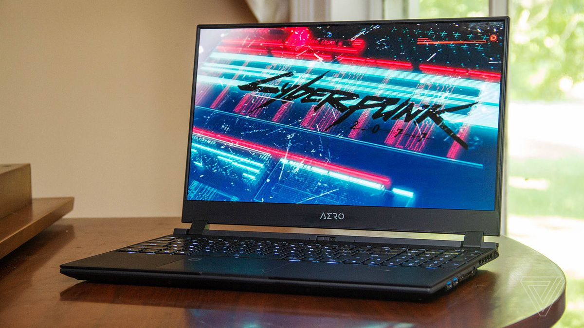 The Gigabyte Aero 15 OLED XD sits on a piano angled to the left. The screen displays the opening screen to Cyberpunk 2077.