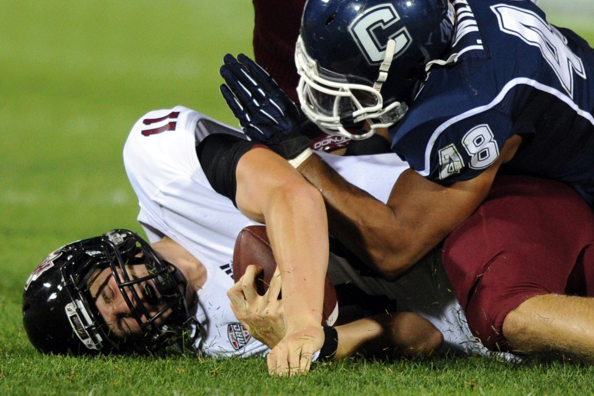 August 30, 2012; East Hartford, CT, USA; Massachusetts Minutemen quarterback Mike Wegzyn is sacked by Connecticut Huskies defensive end Trevardo Williams (48) during the fourth quarter at Rentschler Field. Mandatory Credit: Michael Ivins-US Presswire
