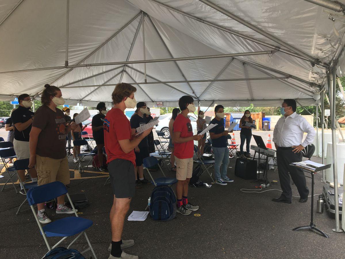 Regis University choir students rehearse under white awning during coronavirus pandemic.