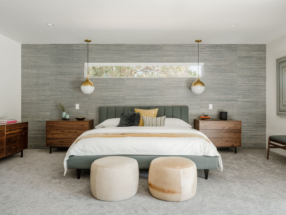 A master bedroom with a king size bed, two side tables, and pendant lighting.