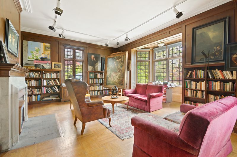 Library with wood-paneled walls and bay windows.
