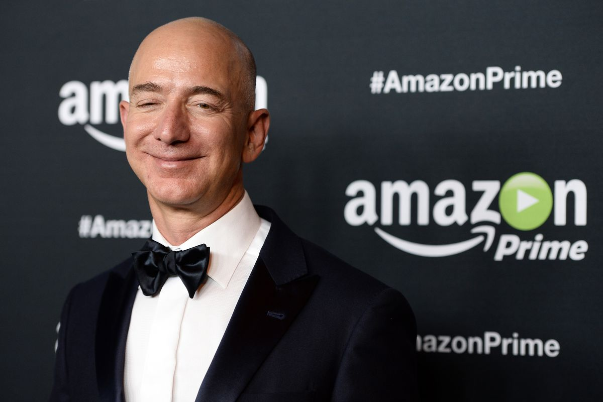 Amazon CEO Jeff Bezos smiling for cameras in front of an Amazon Prime-themed backdrop at an Emmy party in 2015.