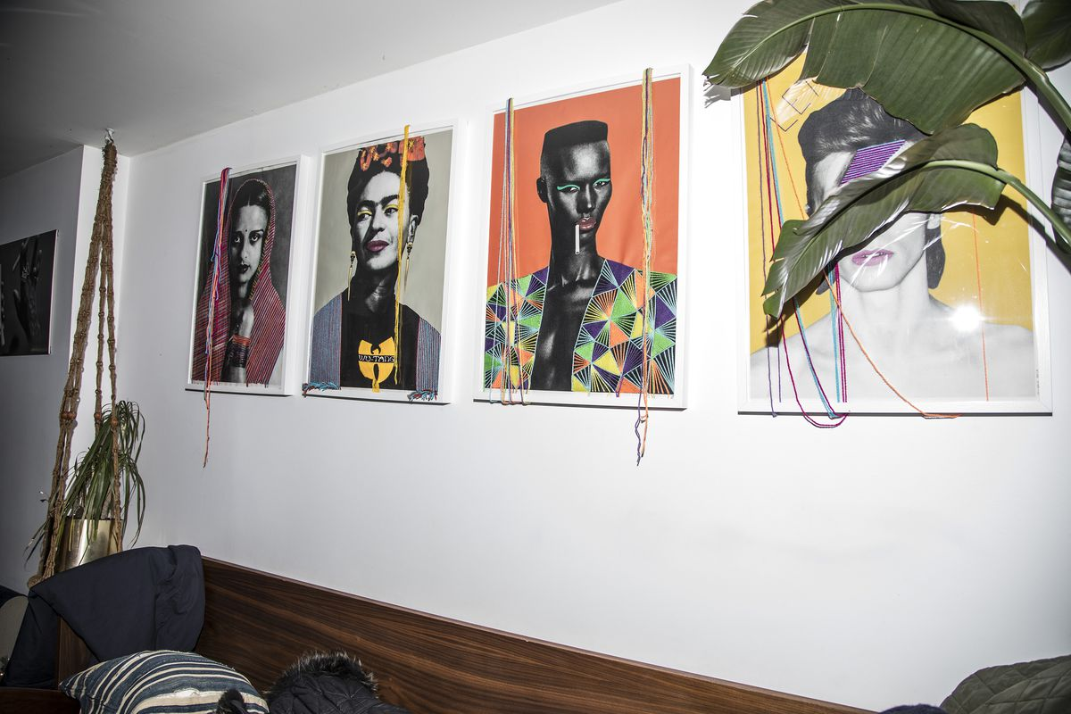A line of pop art portraits of notable figures, Grace Jones, David Bowie and more hanging above a bench at Ode to Babel.