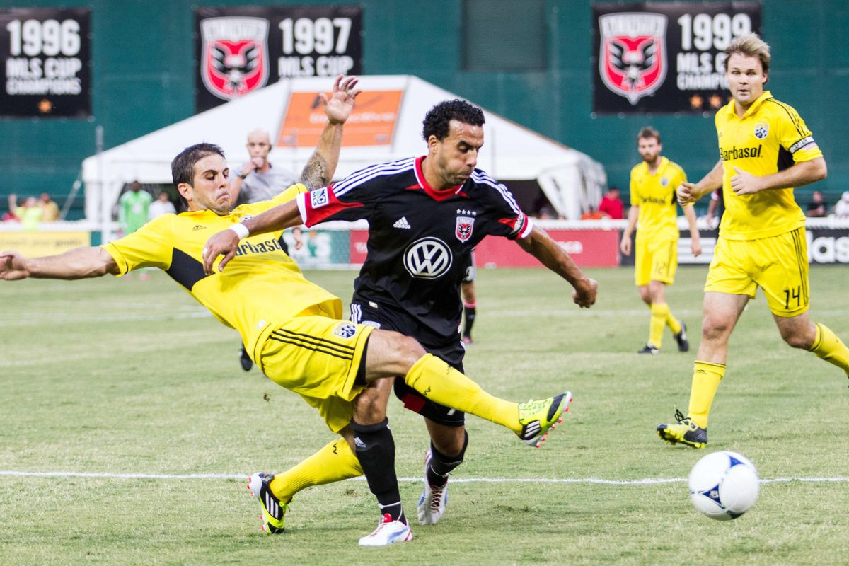 Aug 4, 2012; Washington, DC, USA; DC United midfielder Dwayne De Rosario (7) has the ball tackled away from him by Columbus Crew defender during the first half at RFK Stadium.  Mandatory Credit: Paul Frederiksen-US PRESSWIRE