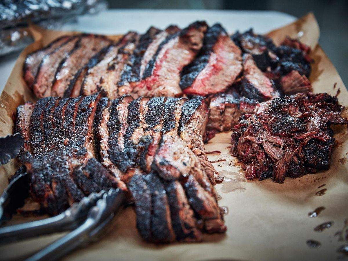 A giant cutting board covered in brown butcher paper is overwhelmed by an abundance of barbecued brisket with a nice, dark bark and tender pink insides oozing juices