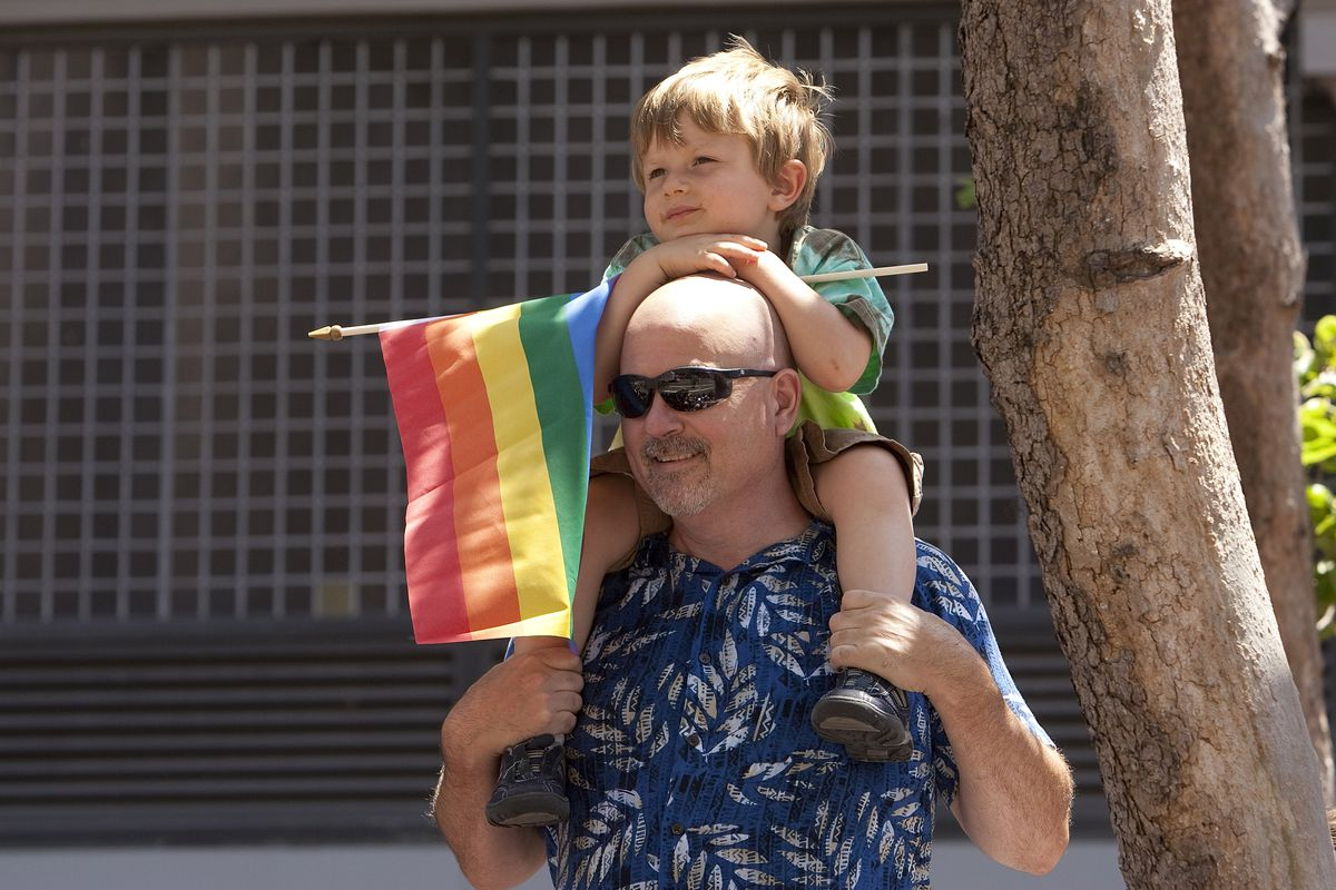 A man and his son watch the LGBT Pride Parade in San Francisco.
