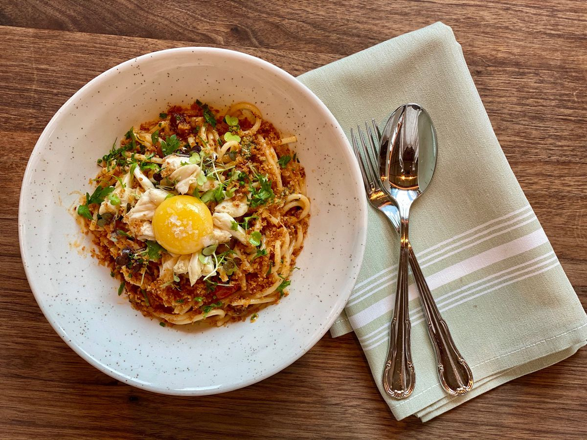 Blue crab carbonara in a white bowl topped with an egg yolk