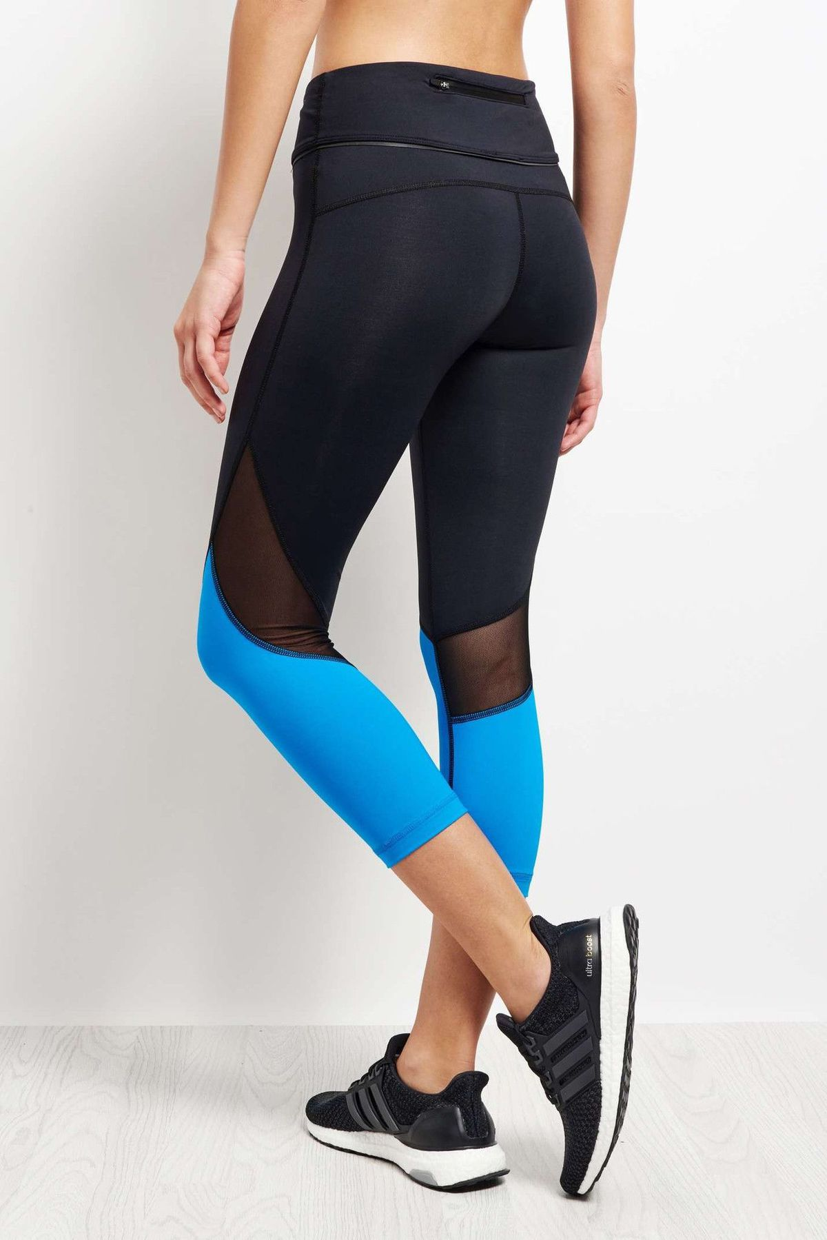1fb609c67628a A woman in black and blue workout capris with mesh detail