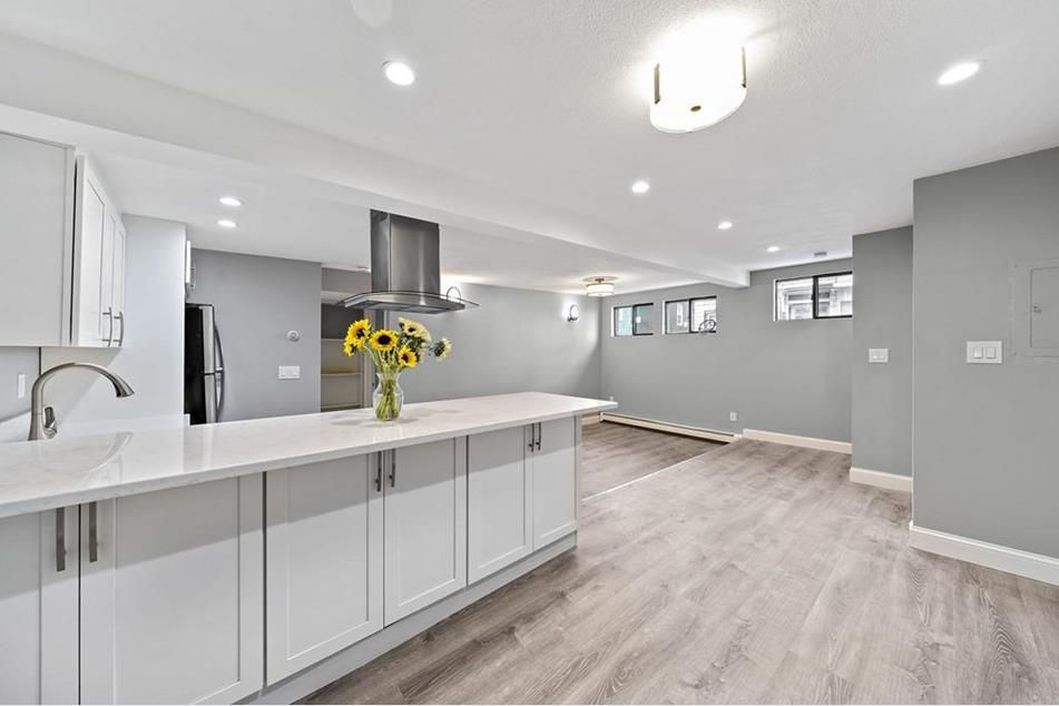 An expansive, open dining room area next to a kitchen and there's a single bunch of sunflowers on the kitchen counter.