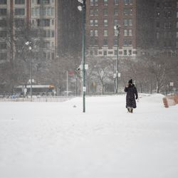A person takes pictures along the Lakefront Trail at Oak Street Beach in the Loop, Tuesday morning, Jan. 26, 2021. Three inches of snow enveloped Chicago as the winter storm passed through northern Illinois.