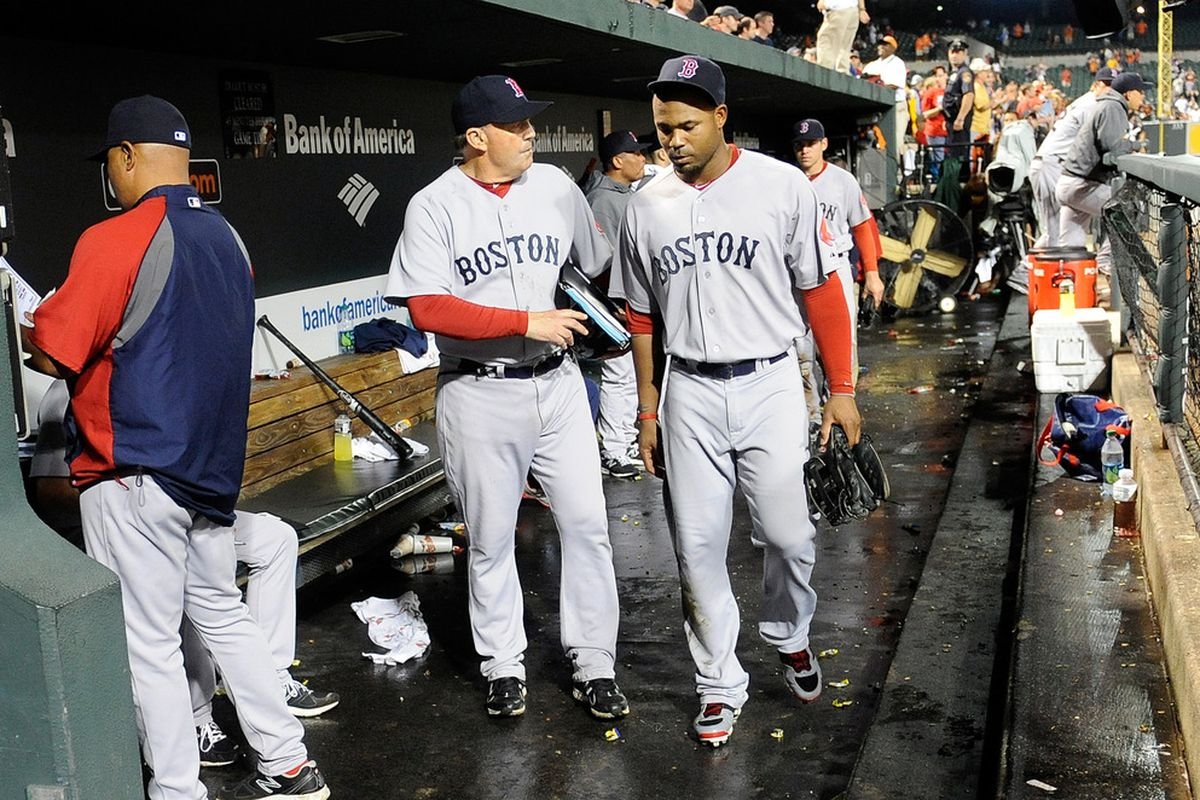BALTIMORE, MD -  Carl Crawford #13 of the Boston Red Sox walks in the dugout with first base coach Ron Johnson #50 after a 4-3 loss against the Baltimore Orioles at Oriole Park at Camden Yards.  (Photo by Greg Fiume/Getty Images)