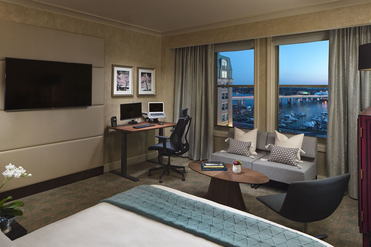 A luxury hotel room with a view and a desk set up with a workstation and an ergonomic chair.