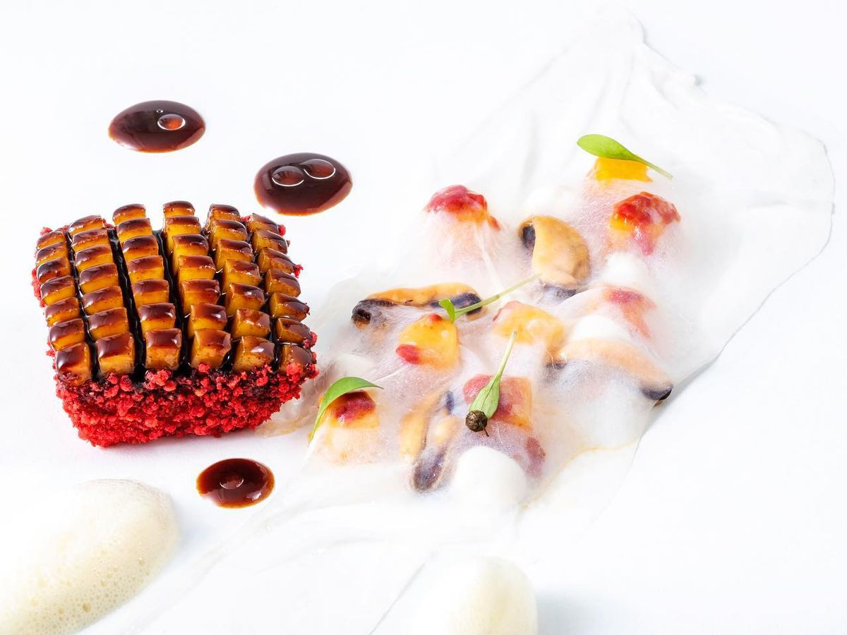 Geometrically sliced squid with a bright red crust sits beside chunks of more squid, flowers, and mango slices beneath a white foam.