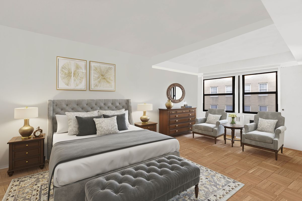 A bedroom with hardwood floors, a large bed, two windows, two couches, and wooden furniture.