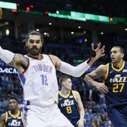 Oklahoma City Thunder center Steven Adams (12) grabs a rebound in front of Utah Jazz center Rudy Gobert (27) in the first quarter of an NBA basketball game in Oklahoma City, Tuesday, Dec. 5, 2017. Oklahoma City won 100-94. (AP Photo/Sue Ogrocki)