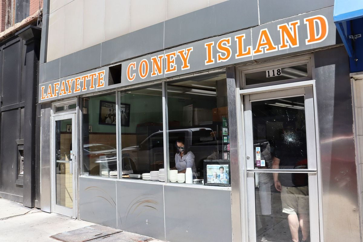 Gretchen Whitmer is seen at the grill preparing coneys through the window below the Lafayette Coney Island sign.