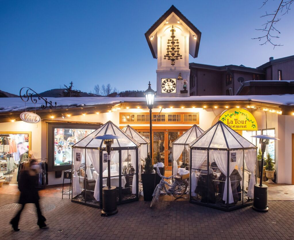 A series of outdoor dining igloos, some with diners inside, outside of a restaurant with a clock tower
