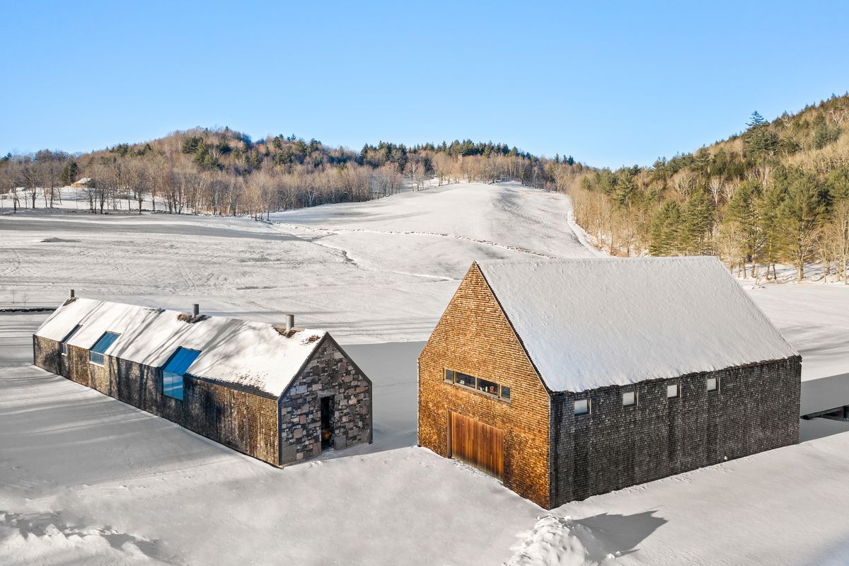 A long stone house sits next to a large barn in the snow.