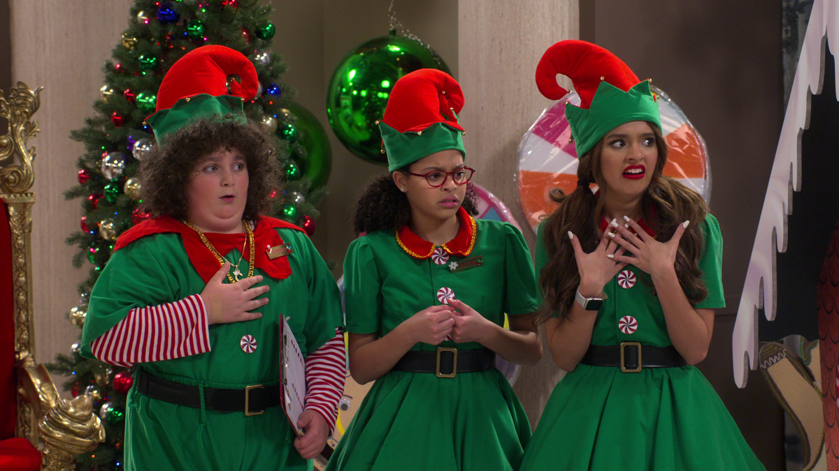 three students in elf costumes, looking various states of disturbed. the one on the far left has curly hair and looks mildly confused, while the one on the far right looks extremely shocked. the middle one is like middle confused