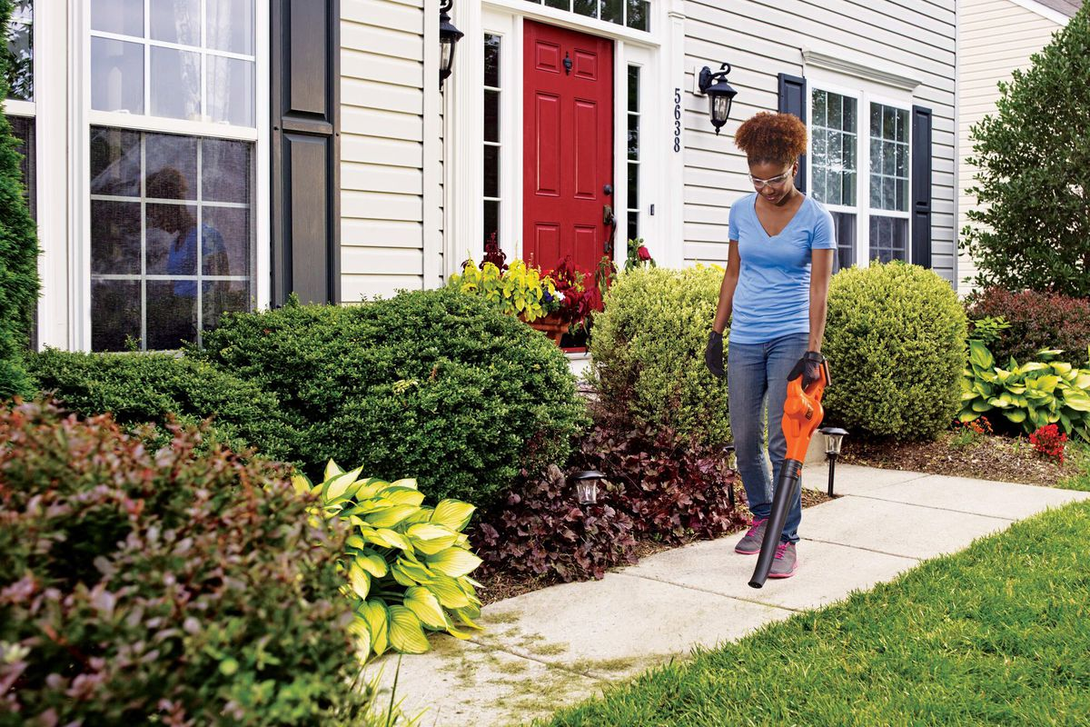 A woman using a leaf blower to clean the front path of her house