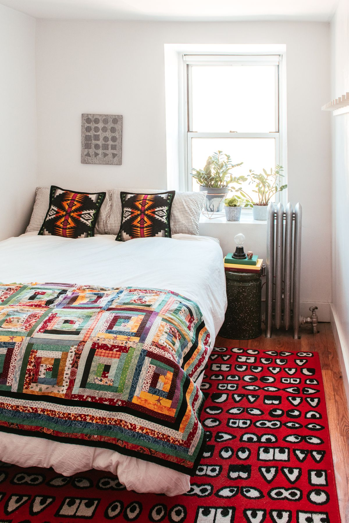 A bedroom with a bed and an end table. The bed has a patterned quilt and assorted throw pillows. There is a patterned area rug on the floor. There are multiple houseplants in the window will next to the bed.