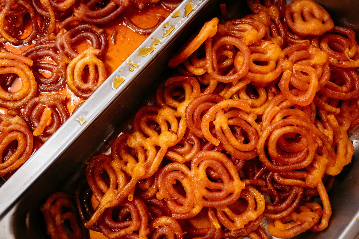 Bright orange funnel-cake like fried desserts soaked in syrup sit in a metal pan.