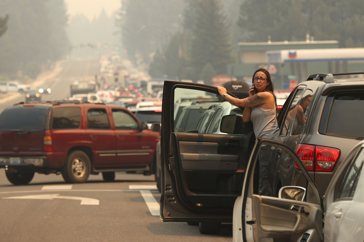 A woman talks on her phone while stopped in heavy traffic on Hwy 50 as people evacuate ahead of the Caldor Fire on August 30, 2021, in South Lake Tahoe, California.